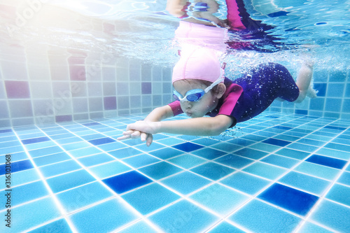 Obraz na plátně Underwater young little cute girl is swimming in the swimming pool with her swimming teacher