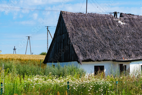 One old thatched cottage in field