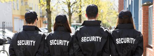 Obraz na płótnie Rear View Of Security Guards Standing In A Row