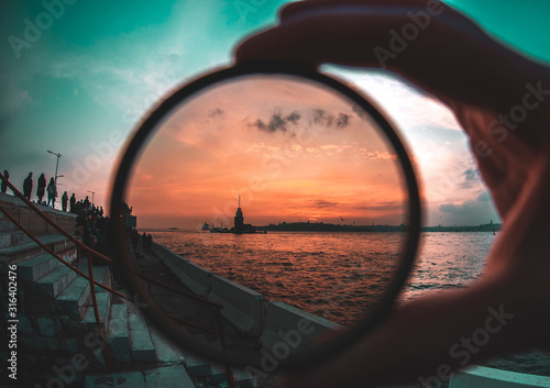 Foto a man holding a photo filter with backgorund of Maiden Tower during sunset
