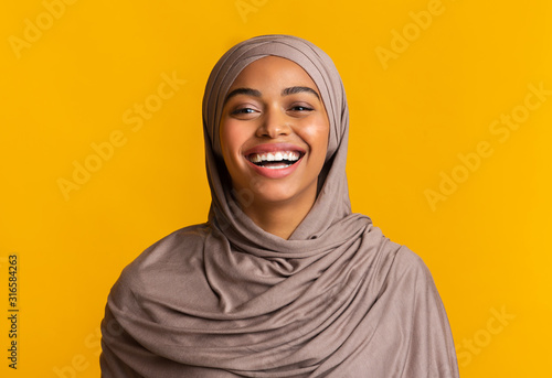 Canvas Print Portrait of sincerely laughing black muslim woman over yellow background