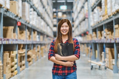 Leinwand Poster Portrait of Asian woman warehouse worker standing and holding the clipboard for