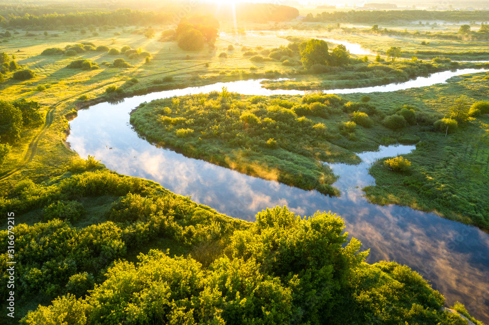 Summer morning on the river with fog, aerial view. River located between forest and green fields