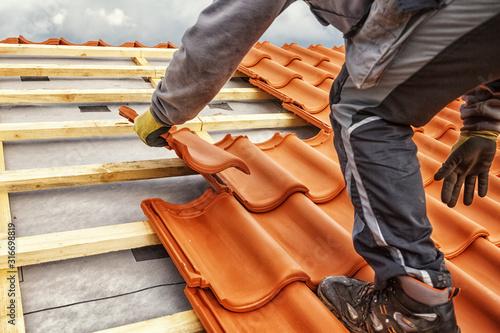 Fotografie, Obraz Roofer at work, installing clay roof tiles, Germany