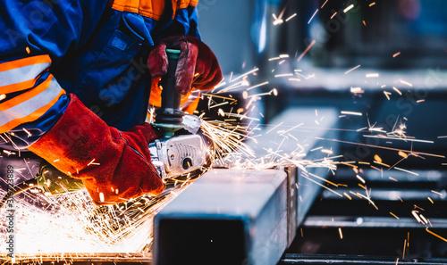 Fotografia Worker grinding in a workshop. Heavy industry factory