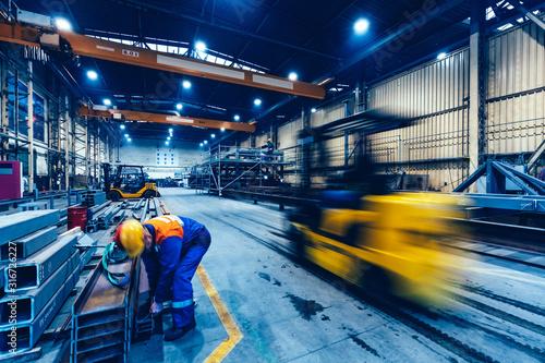 Obraz na plátně Factory work. Forklift moving and a worker taking a steel profile