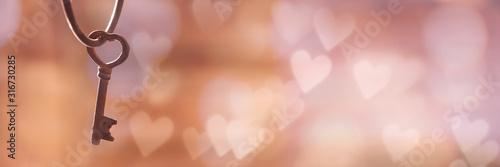 Stary ośniedziały rocznika klucz w formie serca, panoramiczny bokeh tło z kopii przestrzenią. Baner internetowy miłości i Walentynki