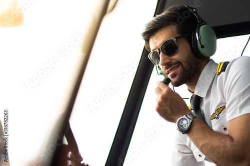 Fotografija Pilot with headset starting the controls in cockpit helicopter