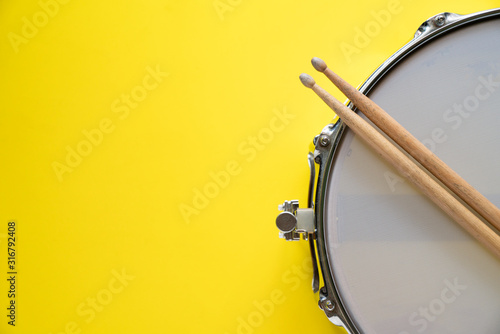 Fényképezés Drum stick and drum on yellow table background, top view, music concept