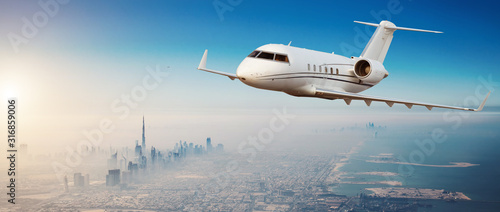 Fotografie, Obraz Private jet plane flying above Dubai city