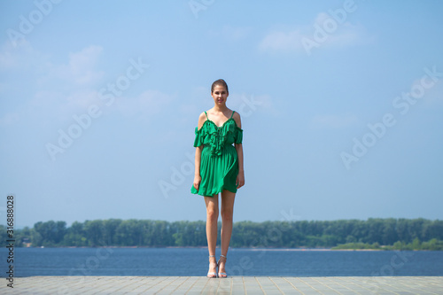 Stampa su Tela Young beautiful brunette girl in green dress walks along the embankment of the r
