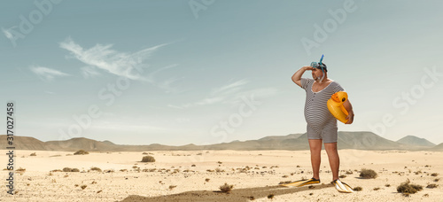 Fotografia Funny overweight swimmer looking for the beach  in the middle of the desert with