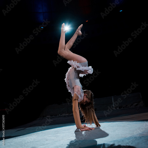 girl in costume doing handstand while performing in arena of circus Fototapet