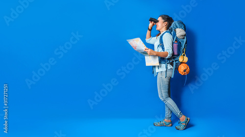 Canvas-taulu Young asian traveler happy woman in Blue shirt with backpack with and equipment for travelers Vacation with a map, on Blue color background