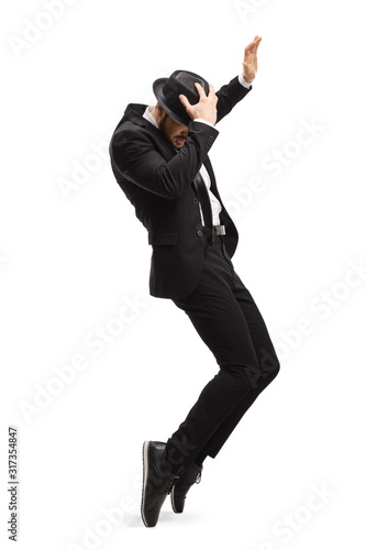 Fotografia Young man in a suit dancing and holding his hat