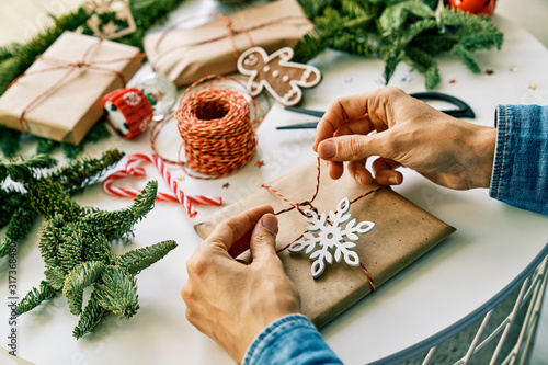 Cropped anonymous person hands wrapping preparing christmas gifts with rope and christmas decorations