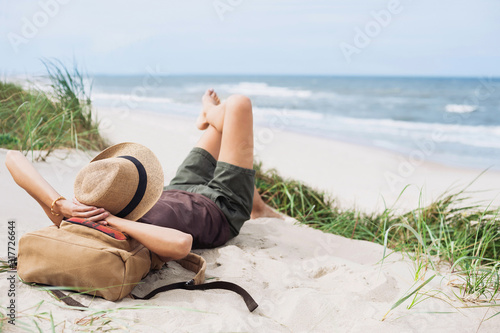 Young woman resting by the sea. Girl lying down on the beach. Enjoying life, summer lifestyle, relaxation, mindfulness and travel concept
