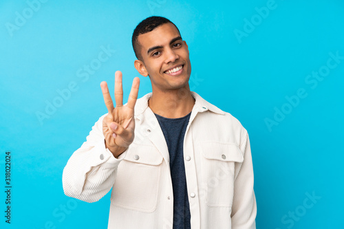 Fotografia, Obraz Young African American man over isolated blue background happy and counting thre