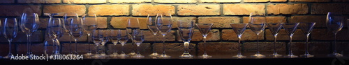Fototapeta premium Glasses against the backdrop of an illuminated brick wall