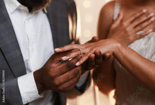 Fotografia Close up of afro man putting ring on woman finger