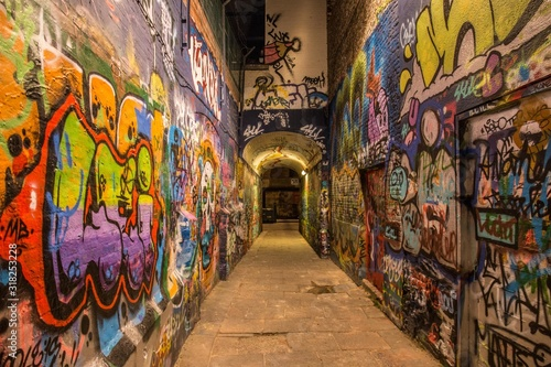 Arch in a narrow street with colorful graffiti all over the walls