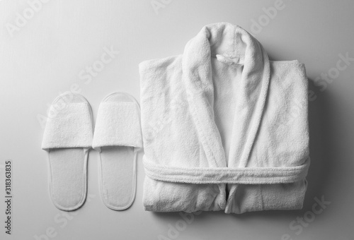 Photo Clean folded bathrobe and slippers on white background, flat lay