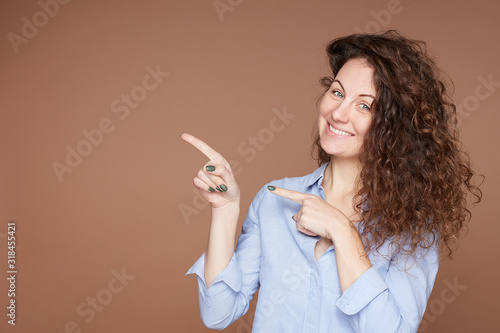 Slika na platnu Curly headed lovely woman with pleasant look shows blank copy space for advertisement or information, has cheerful face expression, wears blue jacket, suggests to select option over pastel beige wall