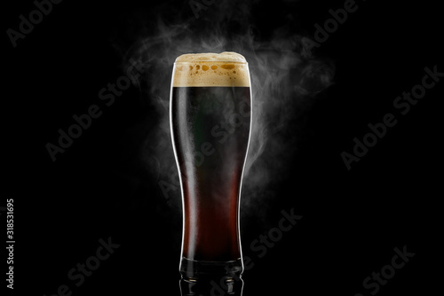 Photo Cold pilsner beer glass with black porter beer inside covered with drops and froth evaporating on black background