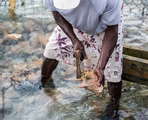 Midsection Of Man Breaking Seashell In Sea Fototapet