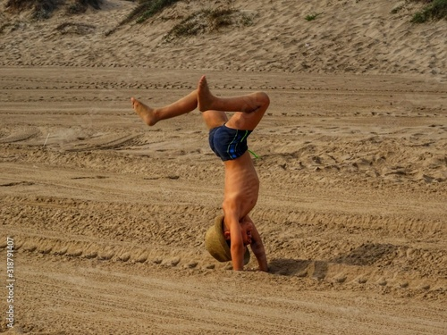 Valokuvatapetti Full Length Of Shirtless Boy Practicing Handstand On Sand