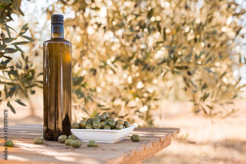 Fotografia green olives and oil on table in olive grove