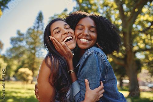 Close up lifestyle portrait of diverse multiracial happy best friends hugging ea Fototapet