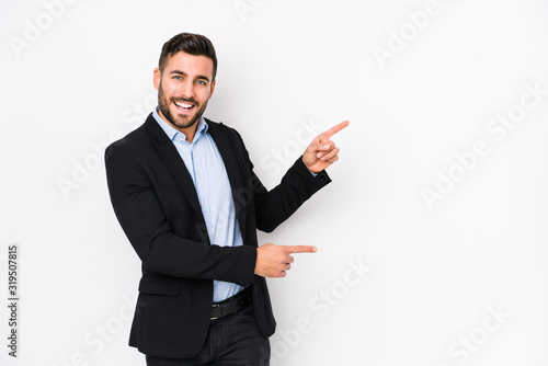 Valokuvatapetti Young caucasian business man against a white background isolated excited pointing with forefingers away