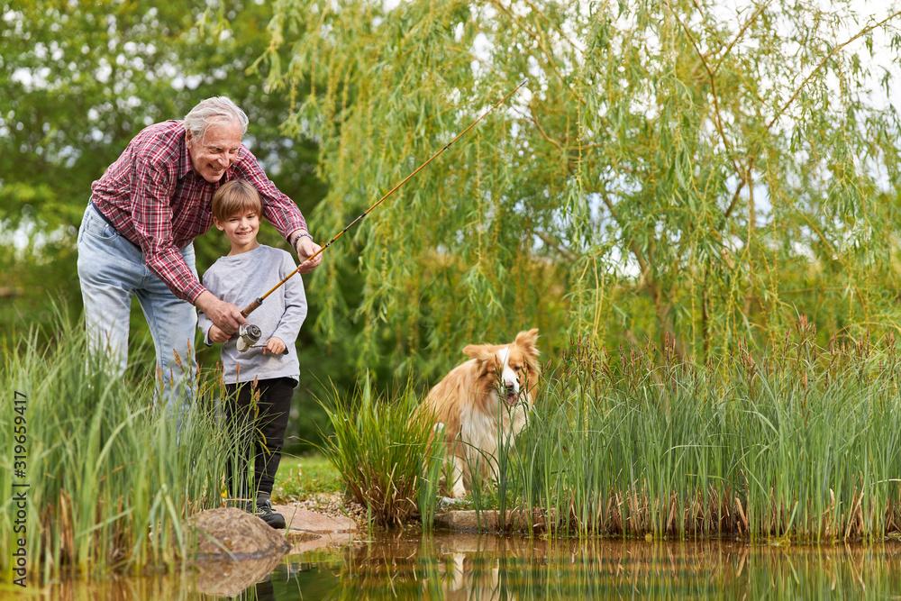 Großvatern beim Angeln mit Enkelsohn am See <span>plik: #319659417   autor: Robert Kneschke</span>