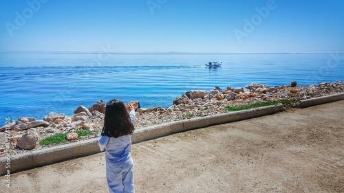 Fotografie, Obraz Rear View Of Little Girl Waving On Promenade By Sea Against Clear Sky