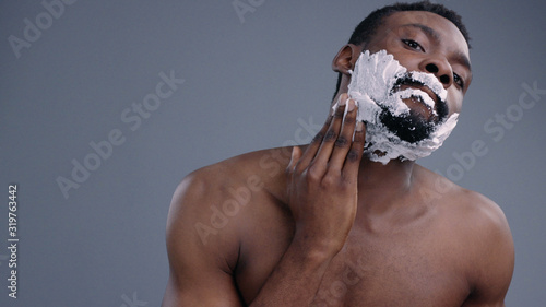 Photographie Close-up of handsome young afro-american shirtless man shaving and applying cream on his face