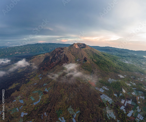 Spectacular aerial view of Mount Batur volcano on Bali, Indonesia with small clouds on the foot of the mountain Fototapete