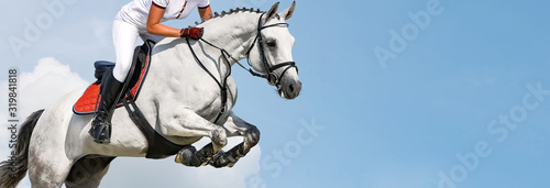Obraz na plátně Girl jumping with white horse, isolated, blue sky, white clouds background