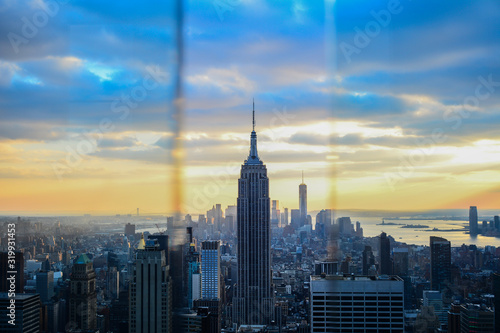 Empire State Building in city against cloudy sky seen through window during suns Fototapeta