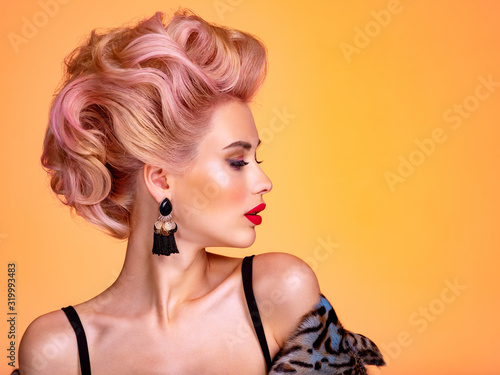 Beautiful woman with creative hairstyle, vivid makeup. Fashionable girl. Beautiful face of young woman with red lips. Stunning blonde girl. Bright eye makeup. Attractive caucasian model with earrings