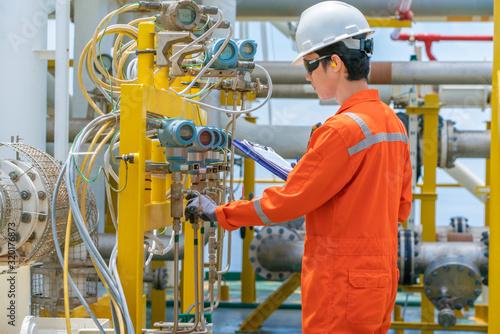 Fotografering Technician operator checking and record reading value of pressure, temperature a