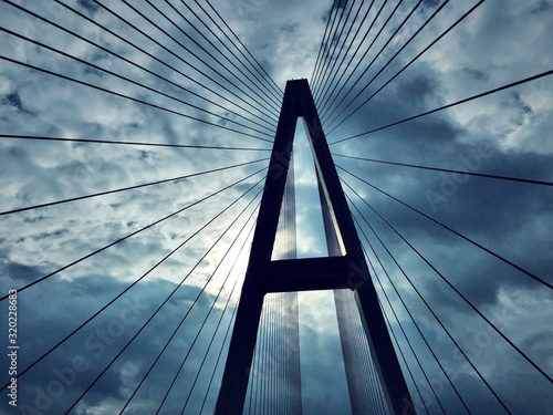 Low angle view of bridge cables against clouds