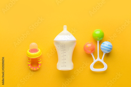 Obraz na plátně Bottle of milk for baby and toy with pacifier on color background