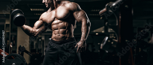 Canvas Print Muscular man bodybuilder training in gym and posing