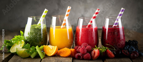 Stampa su Tela Selection of colorful smoothies and ingredients in glasses, rustic background
