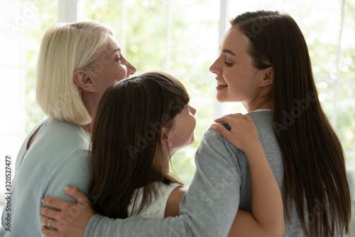 Stampa su Tela Happy three generations of women hug showing unity