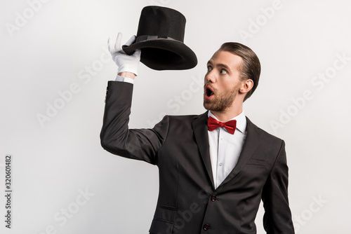 Photo shocked magician with open mouth looking at hat, isolated on grey