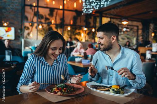 Tableau sur Toile romantic couple in restaurant having lunch