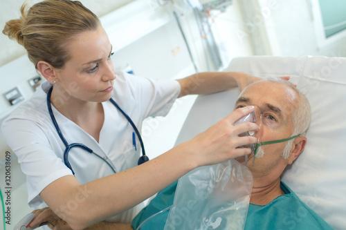 female doctor applying oxygen mask on senior patient Fototapeta