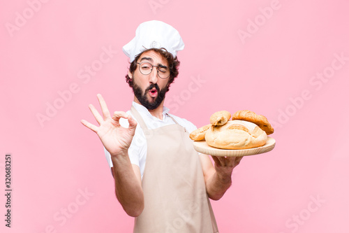 Photographie young crazy baker man holding bread against pink wall